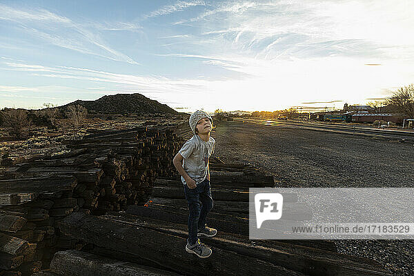 7 year old boy standing alone on railroad ties at sunset