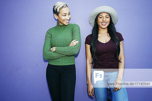 Two young women standing side by side against a plain background