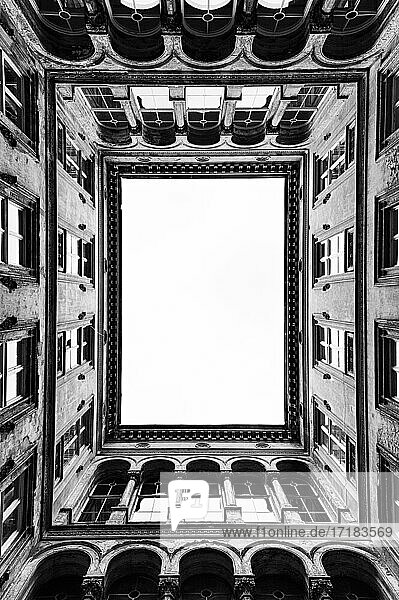 Architecture,  the central courtyard of a tall historic building,  windows and cornicing.