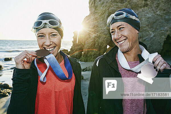 Two sisters  triathletes in training in swimwear wearing their large medals  winners.