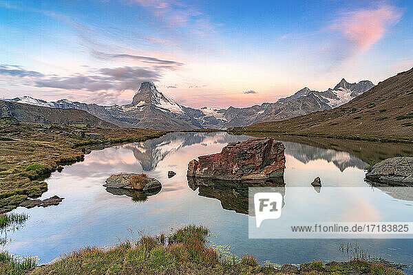Pink sky at dawn over Matterhorn reflected in lake Stellisee  Zermatt  Valais Canton  Switzerland  Europe