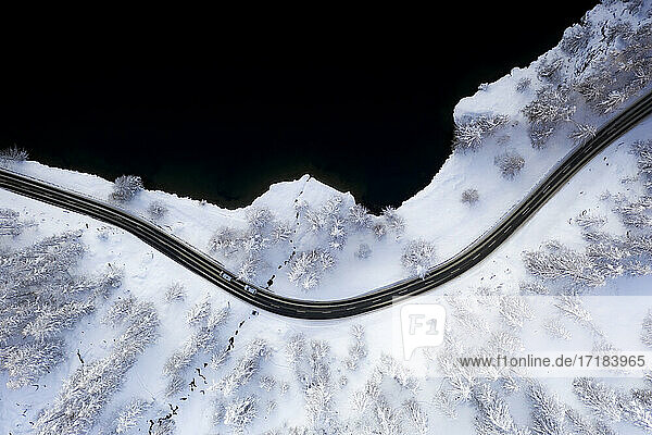 Cars traveling on snowy road on shore of Lake Sils from above  Engadine  Graubunden Canton  Switzerland  Europe