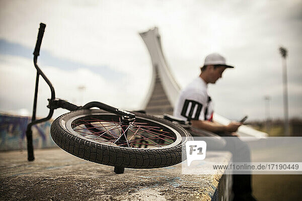 Bmxer sitting on top of ramp using mobile phone