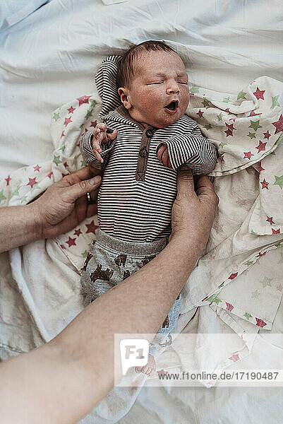 Newborn baby boy in coming home outfit held by dad on hospital bed