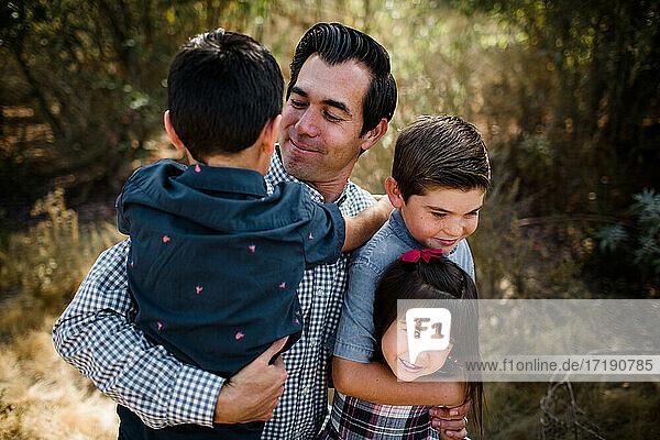Dad Holding Three Children in Field in San Diego