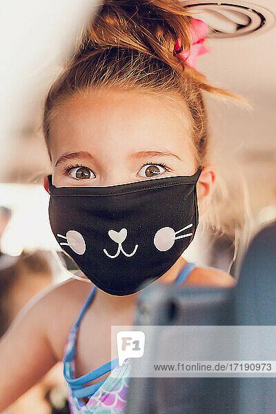 Pretty girl wearing a mask inside a car.