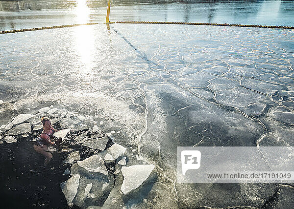 Woman Holding Solid Ice While Floating In Frozen Ocean in Denmark