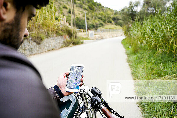 Man holding smartphone with road map  sitting on vintage motorbike