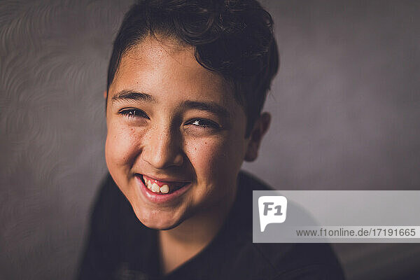 Portrait of a boy smiling at the camera.