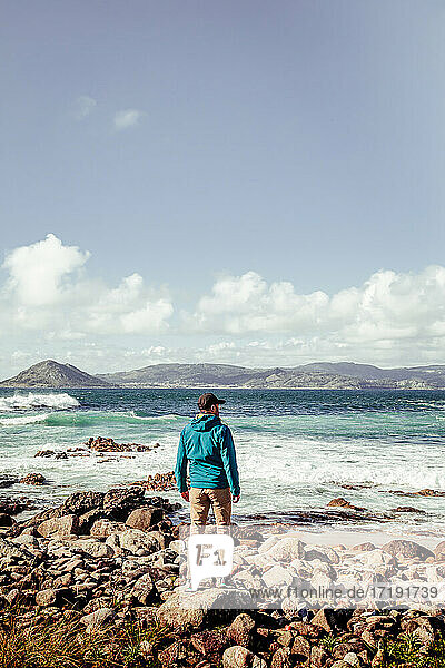 Man in blue jacket and black cap looking at the sea