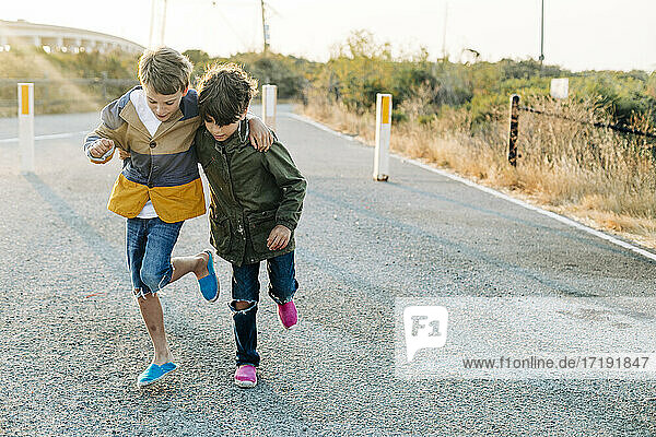 Boys helping each other to walk in one leg by entrance park at sunrise
