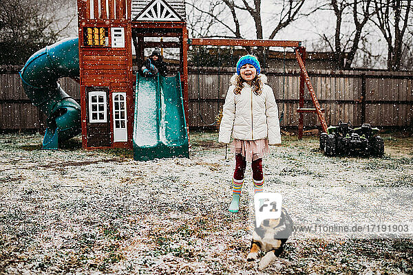 Two young kids and puppy playing in backyard on snowy day