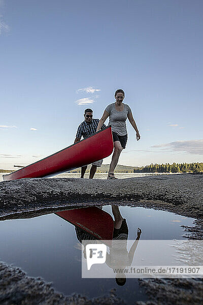 Man and woman reflected in puddle haul red canoe out of lake in Maine