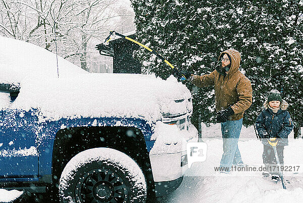Father and son clearing the snow together in driveway in Massachusetts