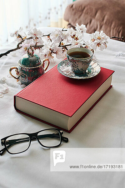 Still life of a book  coffee cups and almond blossoms. Reading concept