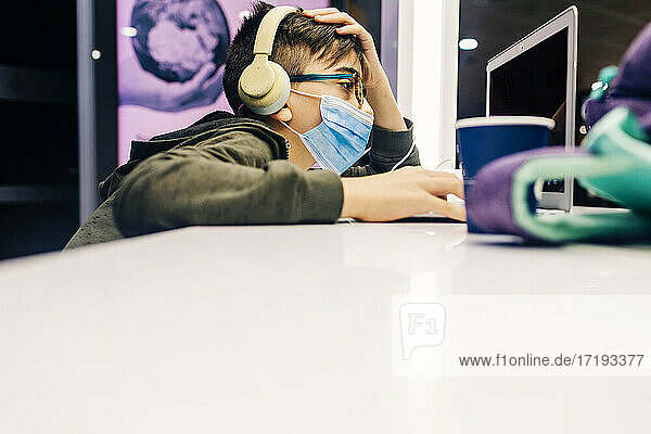 Pre-teen wearing mask attends online classes in airport terminal