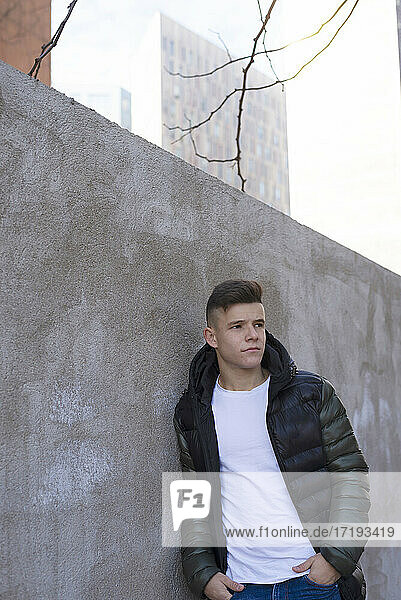 Young man leaning on concrete wall hands on pocket. looking at camera
