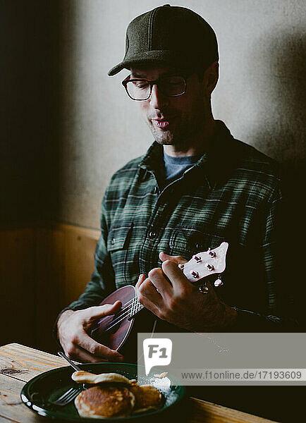 A man wearing flannel shirt plays ukulele during pancake breakfast
