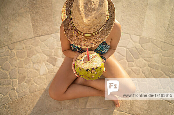 Happy woman relaxing in the swimming pool and drinking coconut water.