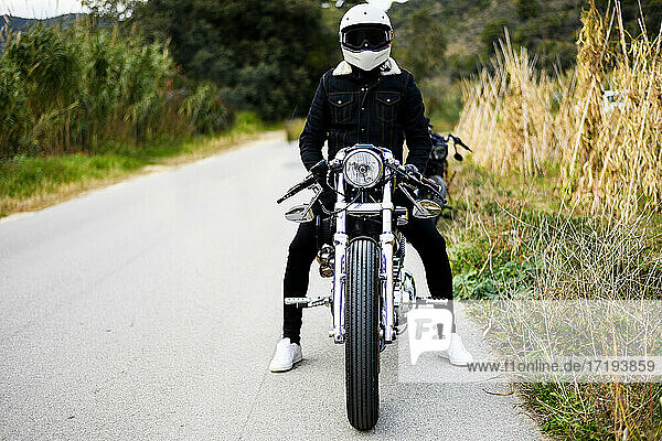Front view of a motorcycle stands on the road with its owner alone