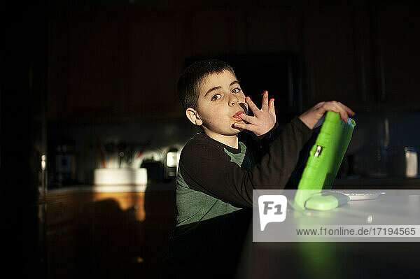 Boy 9-10 years old licks fingers while holding tablet in pretty light