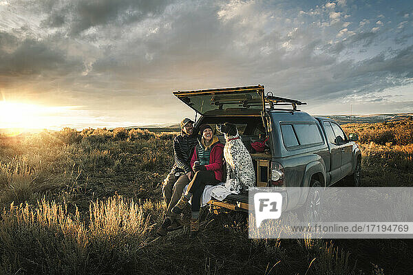 Cheerful couple sitting with dog at trunk of off-road vehicle on field during vacation