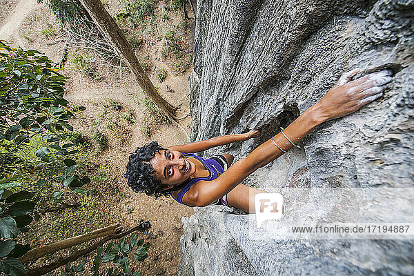 high angle view of woman climbing steep limestone cliff in Laos