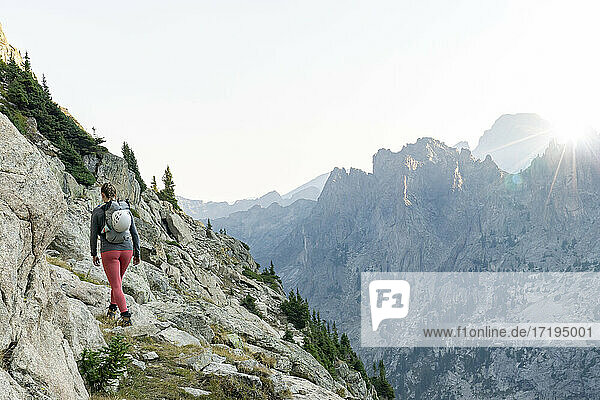 Rear view of woman hiking on mountain against clear sky during vacation