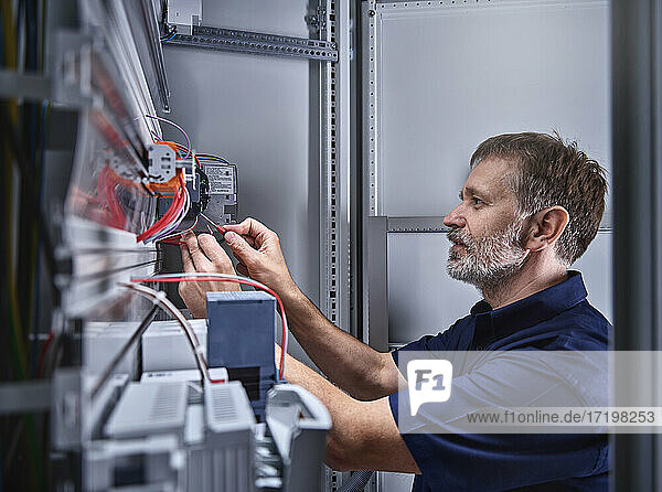 Male electrician examining power supply in electrical workshop