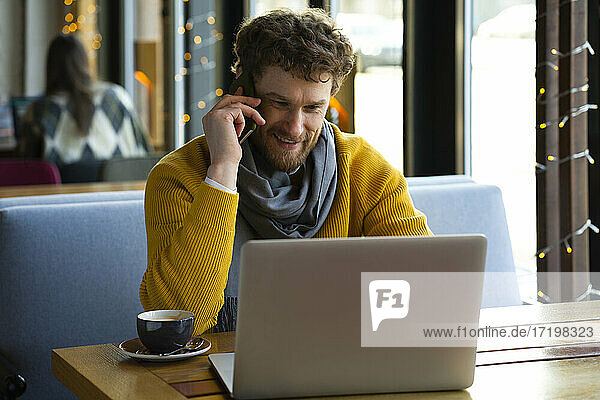 Handsome businessman talking on mobile phone while using laptop at cafe