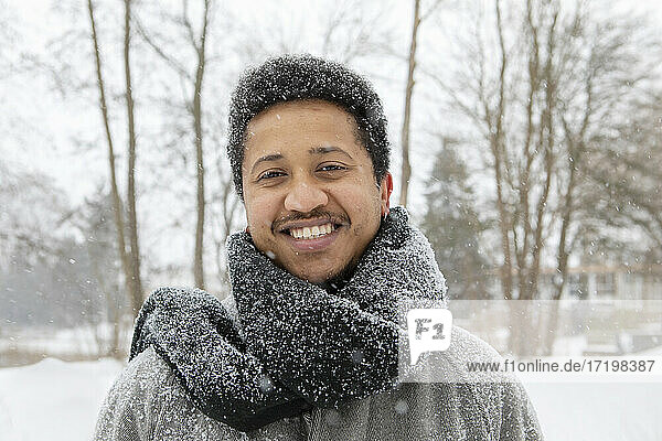 Curly haired man with scarf around neck during winter