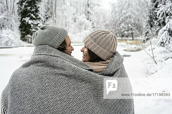 Smiling couple covered in blanket sitting by frozen river in forest