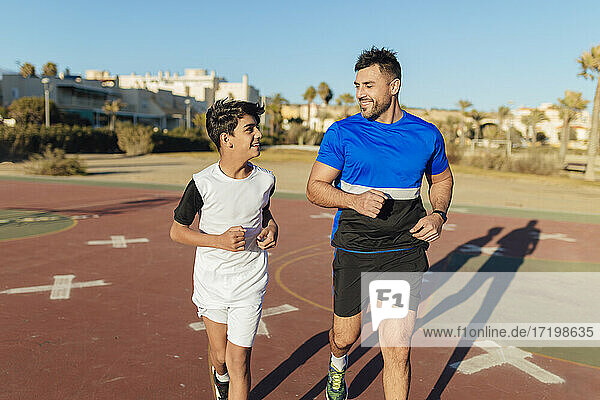Smiling father looking at son while running on sports court