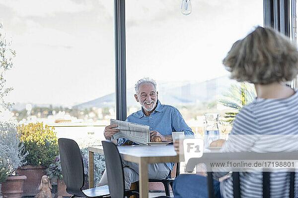 Lächelnder Mann mit Zeitung  der eine Frau ansieht  während er zu Hause sitzt