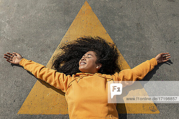 Carefree young woman with eyes closed lying down on footpath