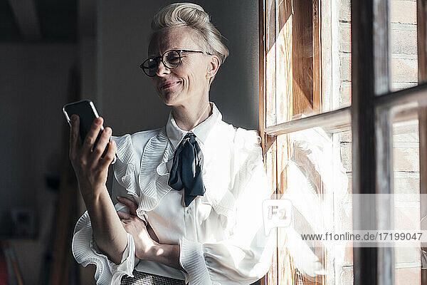 Lächelnde Geschäftsfrau  die auf ihr Mobiltelefon schaut  während sie am Fenster im Büro zu Hause steht