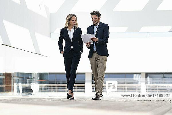Geschäftsfrau  die mit einem Kollegen über Papier diskutiert  während sie auf der Terrasse eines Bürogebäudes spazieren geht