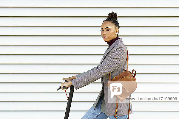 Female entrepreneur carrying bag while standing with electric push scooter in front of white striped wall