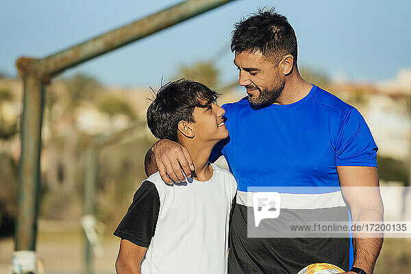 Smiling father with arm around neck of son at sports court