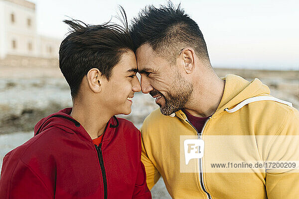 Smiling father and son touching forehead