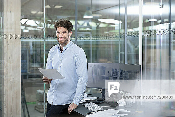 Smiling male entrepreneur with business strategy standing by desk against glass wall in factory