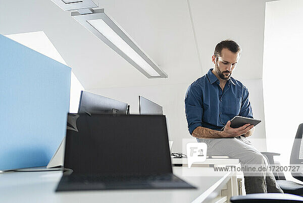 Businessman using digital tablet while sitting at office