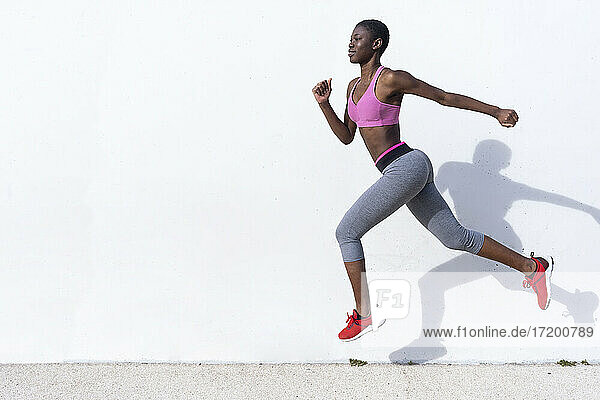 Young woman jumping against white wall during sunny day