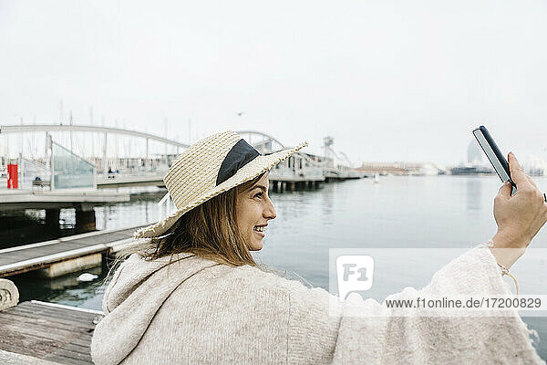 Smiling young woman with hat taking selfie through mobile phone at the waterfront