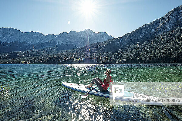 Germany  Bavaria  Garmisch Partenkirchen  Young woman sitting on stand up paddle board on Lake Eibsee and looking at Zugspitze Mountain