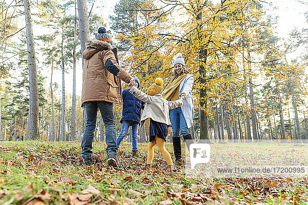Playful parents and children holding hands while playing in forest