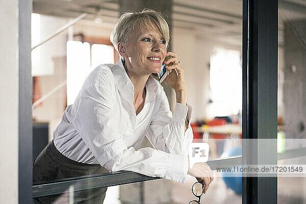 Lächelnde Geschäftsfrau  die mit ihrem Handy telefoniert und sich zu Hause ans Fenster lehnt