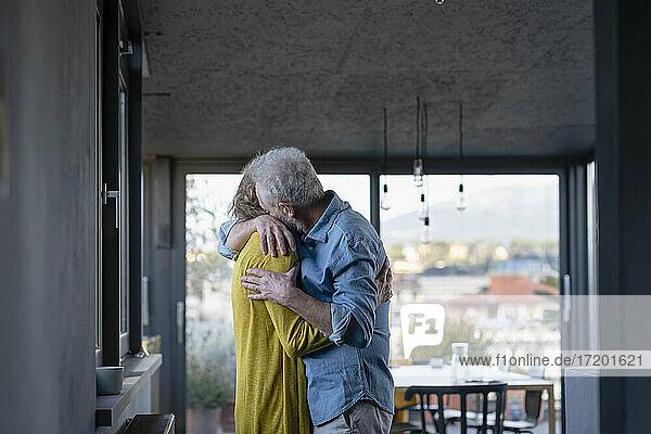 Zärtliches älteres Paar umarmt sich zu Hause stehend