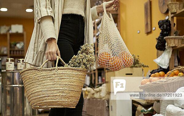 Kräuter und Orangenfrüchte in einer Tüte  die von einer Frau im Geschäft gehalten wird Kräuter und Orangenfrüchte in einer Tüte, die von einer Frau im Geschäft gehalten wird