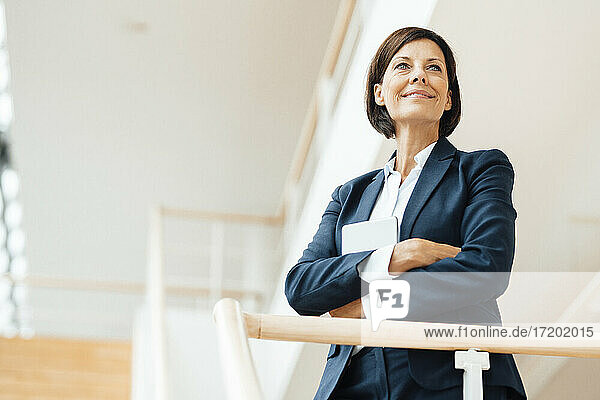 Smiling female entrepreneur with arms crossed standing by railing at office